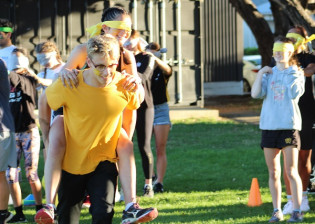 Athletes work together to complete obstacle